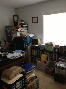 View behind desk of stacked files and clutter.